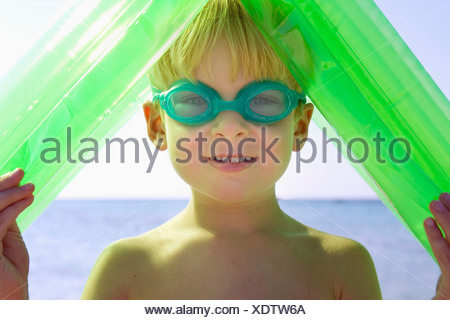 Young boy wearing swim goggles and holding an inflatable raft over his head. - Stock Photo
