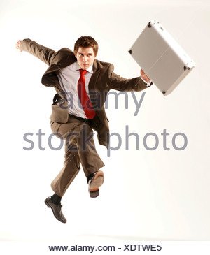 Young businessman carrying a briefcase, jumping in the air - Stock Photo