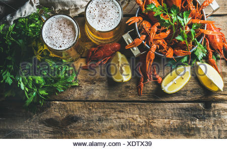 Two mugs of wheat beer and boiled crayfish in pan served with with lemon and parsley over rustic wooden background, top view, co - Stock Photo