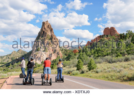 Young people riding Segways in front of Gray Rock or Cathedral Rock, Garden of the Gods, red sandstone rocks, Colorado Springs - Stock Photo