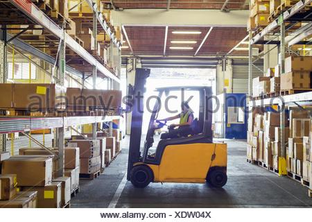 Silhouetted forklift truck at work in distribution warehouse - Stock Photo