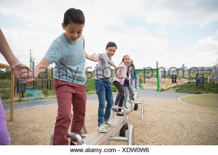Kids balancing on long seesaw at playground - Stock Photo