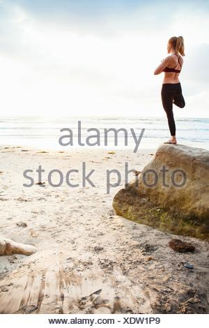 Mid adult woman practicing tree yoga pose on beach rock - Stock Photo