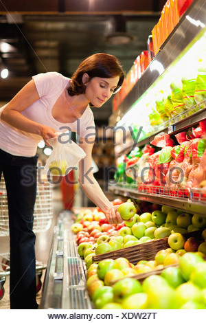 Woman selecting fruit at grocery store - Stock Photo