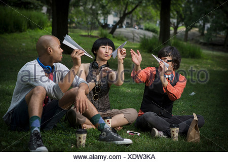 Three friends holding paper planes in park - Stock Photo