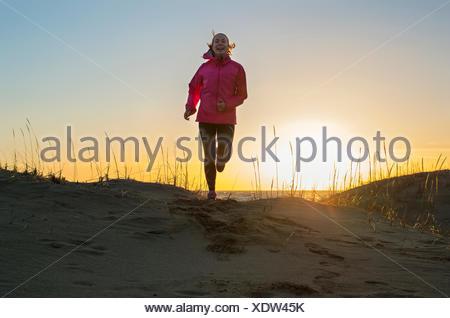 Finland, Pohjanmaa, Pietarsaari, Faboda, Young woman jogging on beach at sunset - Stock Photo