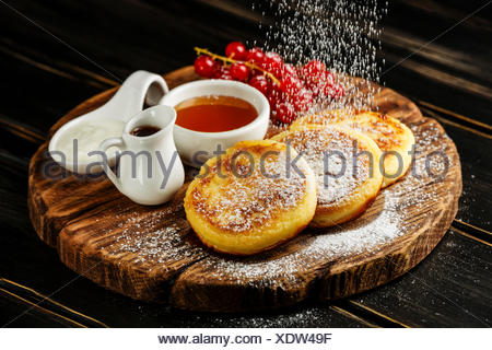 Homemade Cottage cheese pancakes Russian syrniki with sweet sauces on wooden background - Stock Photo