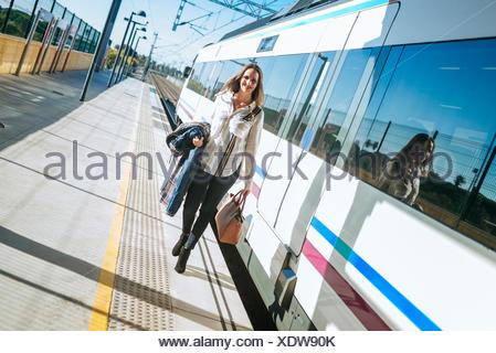 Woman walking on platform next to train - Stock Photo