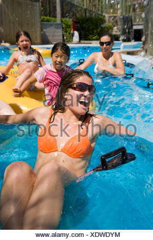 Young women and girls having fun floating on innertubes at water park - Stock Photo
