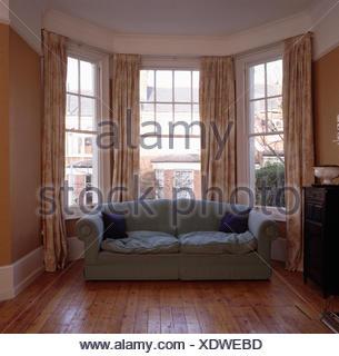 Grey sofa in front of bay window in eighties living room before renovation - Stock Photo