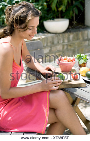 A DayYourself: Profile of female brunette hair tied back loosely wearing short pink sundress orange detail, sitting at wooden - Stock Photo