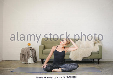A blonde woman in a black leotard and leggings, sitting on a yoga mat in a room.. - Stock Photo