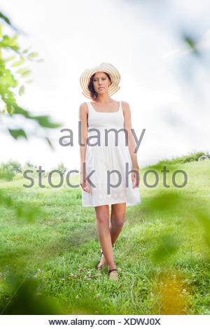Portrait of young woman in sundress and hat walking in park - Stock Photo