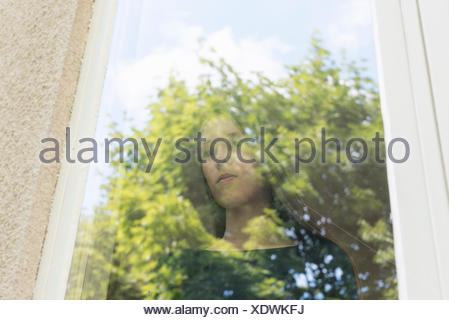 A girl looking out a window - Stock Photo