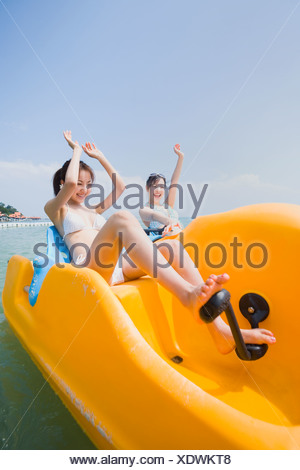 Two young women riding on pedal boat - Stock Photo