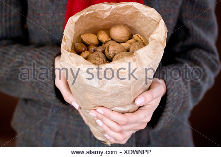 A woman holding a bag full of mixed nuts - Stock Photo