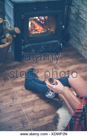 Elevated view of woman sitting in front of a wood burning stove with a glass of wine in hand - Stock Photo