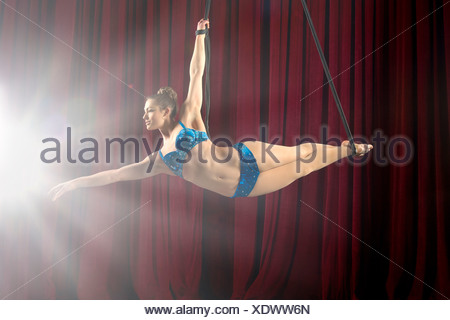 Studio shot of female aerialist poised on ropes - Stock Photo