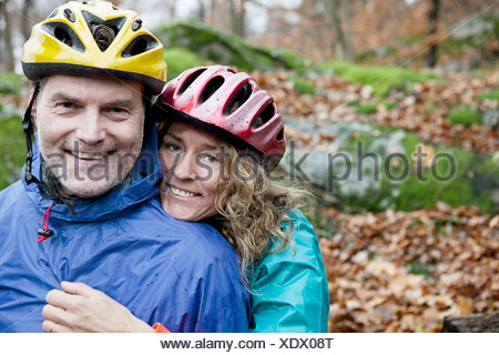 Portrait of mature couple wearing cycling helmets in forest - Stock Photo