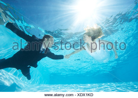 Bride and groom together in pool - Stock Photo