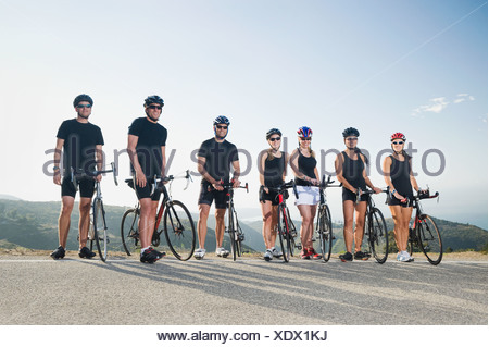 Cyclists standing beside their bikes on the side of the road - Stock Photo