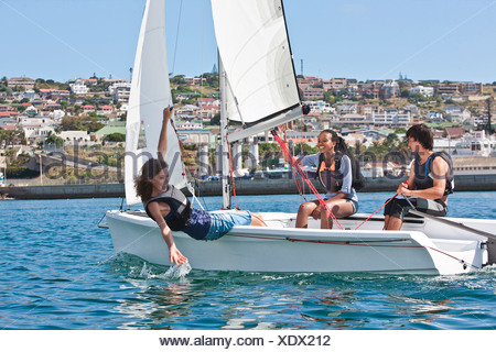 Three young friends sailing in harbor - Stock Photo