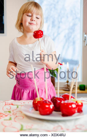 Girl (4-5) holding candied apple - Stock Photo