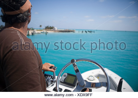 A fisherman steers his boat and hits the throttle from the fly bridge as he gazes out at the blue-green tropical waters. - Stock Photo