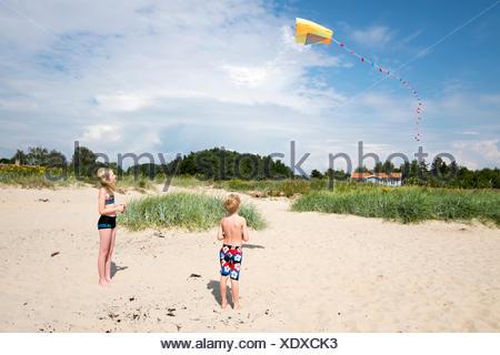 Sweden, Skane, Vejbystrand, Boy (6-7) and girl (10-11) flying kite - Stock Photo