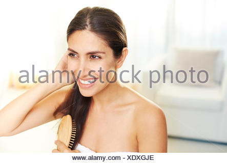 Smiling brunette woman brushing hair - Stock Photo