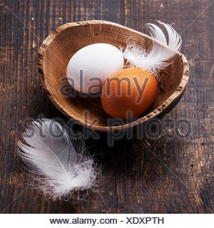 Eggs in bowl on wooden background - Stock Photo