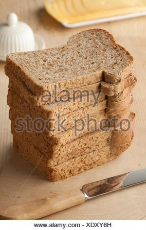 Pile of fresh slices brown bread. - Stock Photo