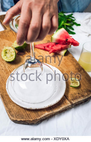 A woman dipping a margarita glass into salt photographed from front view. Lime and watermelon slices accompany. - Stock Photo