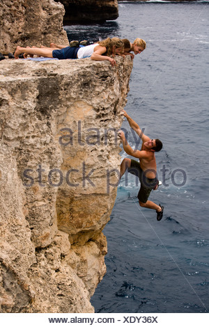 Three women watch a man deep water soloing / rock climbing on a cliff. - Stock Photo