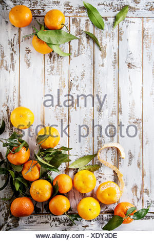 Ripe organic clementines or tangerines with leaves over white wooden plank table as background. Top view, space. Healthy eating - Stock Photo