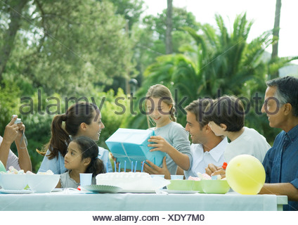 Outdoor birthday party, girl receiving present - Stock Photo