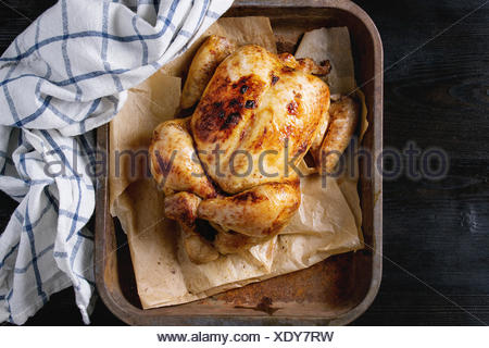 Grilled baked whole organic chicken on backing paper in old oven tray with white kitchen towel over black burnt wooden background. Top view with space - Stock Photo