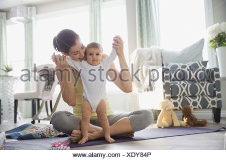 Mother playing with baby girl on yoga mat - Stock Photo