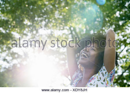 A young woman in a flowered summer dress with her hands behind her head smiling and looking up - Stock Photo