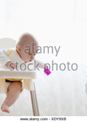 Newborn baby sitting in high chair looking at the ground - Stock Photo
