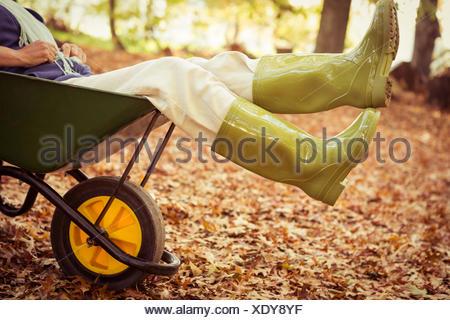 Low section of gardener sitting in wheelbarrow at garden - Stock Photo