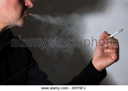 MODEL RELEASED. Man smoking a cigarette exhaling smoke. - Stock Photo