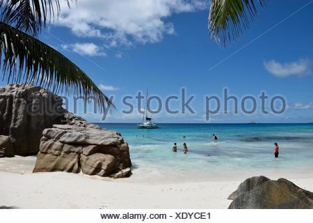Anse Patatas, boat, granite rock, rock, La Digue, sea, water, palms, Seychelles, Africa, beach, seashore, vacationer - Stock Photo