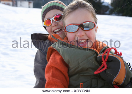 Boy and girl  on sled in snow, wearing sunglasses, smiling, portrait - Stock Photo