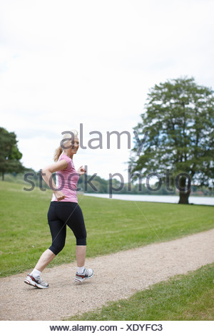 Older woman jogging in park - Stock Photo