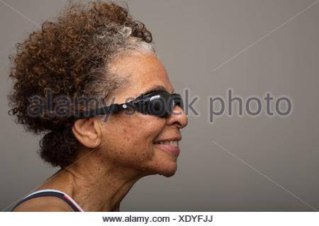 Studio portrait of senior woman in swimming goggles - Stock Photo