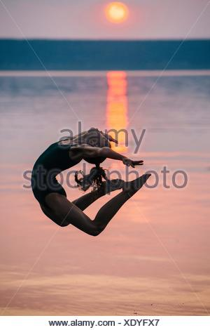 Side view of girl by ocean at sunset, leaping in mid air bending backwards - Stock Photo