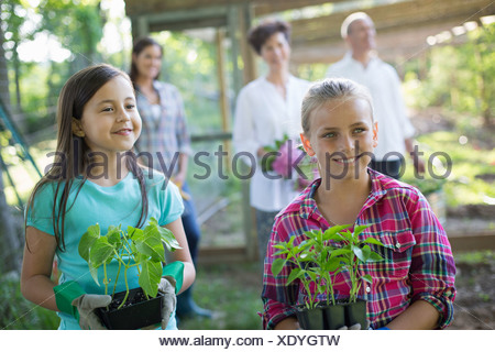 Organic farm. Summer party. Two girls sitting holding young plants, with a mature couple and a young woman looking on. - Stock Photo