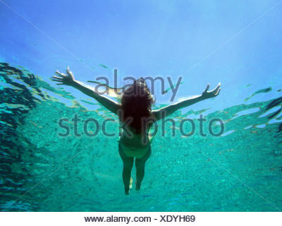 Greece, Dodecanese Prefecture, Chalki, Underwater view of woman floating on water - Stock Photo