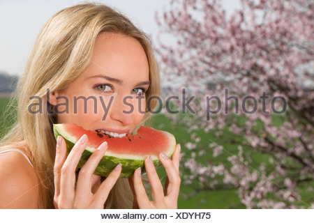 Germany, North Rhine Westphalia, Young woman eating watermelon, smiling, portrait - Stock Photo
